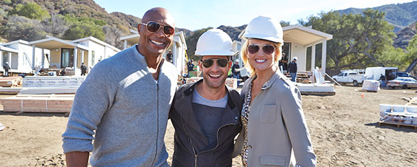 The American Dream Builders host Nate Berkus and judges Monica Pedersen and Eddie George in front of Cavco and Palm Harbor's modular Eco-cottages